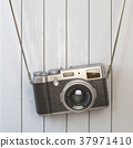 Vintage retro photo camera hanging on  wall. 37971410