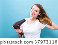 Beautiful woman holding a hairdryer 37973116