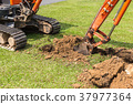 Digger machine operate for digging soil and repair road in the public park 37977364