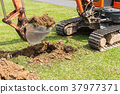 Digger machine operate for digging soil and repair road in the public park 37977371