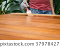 Brush in hand and painting on the wooden table 37978427