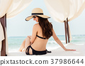 Woman in ocean vacation sitting in beach tent  37986644