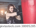 Young caucasian woman doing exercise with Thai boxing (Muay Thai) equipment in gym. Health and fitness concept. 38005285