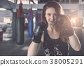 Young caucasian woman doing exercise with Thai boxing (Muay Thai) equipment in gym. Health and fitness concept. 38005291