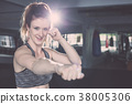 Young caucasian woman doing exercise with Thai boxing (Muay Thai) equipment in gym. Health and fitness concept. 38005306