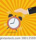 Hand turns off the alarm clock 38013569