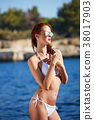 Young adult slim woman in 20s posing on rocks on adriatic sea co 38017903