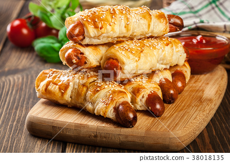 Rolled hot dog sausages baked in puff pastry 38018135