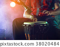 The musician plays the bongo on stage. 38020484