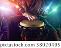 The musician plays the bongo on stage. 38020495