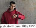 Sport man wearing earphone, looking at his watch  38021855