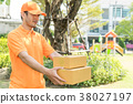 Delivery man in orange handing customer package 38027197