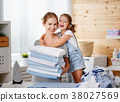 Happy family mother housewife and child daughter ironing clothes 38027569