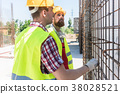 Two workers checking the durability of the steel 38028521