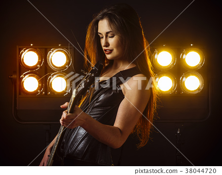 Sexy woman playing electric guitar on stage 38044720