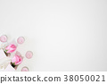 Pink rose flower and candle on white table. 38050021