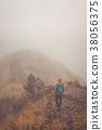 Woman hiker on the cobbled misty path on the 38056375