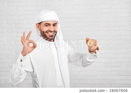 Smiling Muslim man keeps bitcoin on the white 38067606