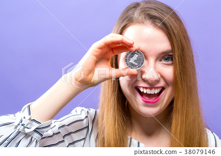 Woman holding a physical Litecoin 38079146