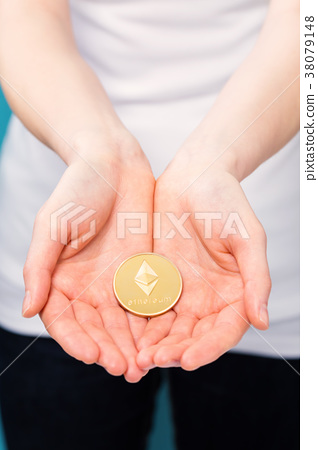 Woman holding a physical ethereum coin 38079148