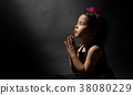 Little girl praying, isolated black background 38080229