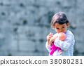 Cute little girl holding and embracing her doll 38080281