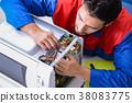 Young repairman fixing and repairing microwave 38083775