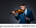 Young man playing violin in dark room 38085563