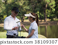 Asian young couple playing golf on golf course 38109307