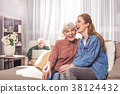 Glad old mother and daughter sitting on sofa 38124432