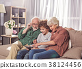 Outgoing grandparents with child watching at 38124456