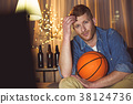 Thoughtful male looking basketball in gadget 38124736