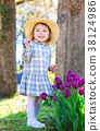 Toddler girl playing with tulips outside 38124986