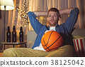Dissatisfied unshaven male looking basketball 38125042