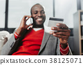 Pleased male with bankcard talking by smartphone 38125071