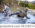 Little boy has a side-slip on the ice 38128414