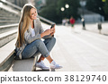 Beautiful young blonde woman looking at her smartphone and smili 38129740