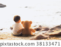 Baby and teddy bear sit togather on the beach 38133471