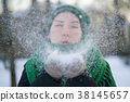 Teen girl blows fresh snow in cold winter day 38145657