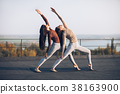 Two beautiful women perform double pose warrior with raised hand 38163900