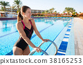 Woman comes out of the sports pool in swimsuit. 38165253