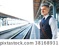 Mature businessman on a train station. 38168931