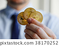 Man holding three Bitcoin coins in hand 38170252