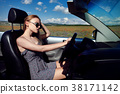 Girl driving a convertible car in a summer poppy 38171142