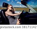Girl driving a convertible car in a summer poppy 38171142