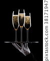Hand with glove holds tray with champagne glasses 38171947