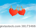 Two hearts hanging on a rope in front of a sky.  38173466