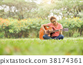 Female is sitting and playing Acoustic Guitar. 38174361