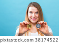 Woman holding physical bitcoin and litecoin 38174522