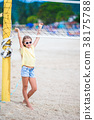 Little adorable girl playing beach volleyball with 38175788